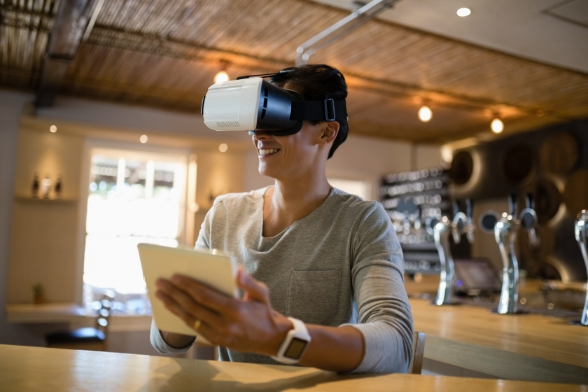 Smiling man using virtual reality headset and digital tablet in